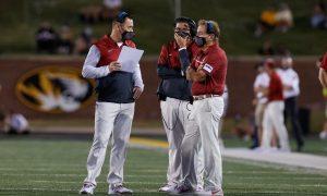 Steve Sarkisian talks to Nick Saban and Jeff Banks on the sideline