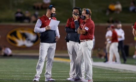 Steve Sarkisian talks to Nick Saban and Jeff Banks on the sideline