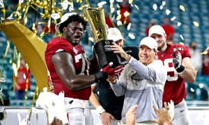 Nick Saban and Alex Leatherwood hold 2021 CFP National Championship trophy for Alabama