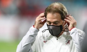 Alabama head coach Nick Saban puts mask on