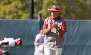 Nick Saban walks along the practice field