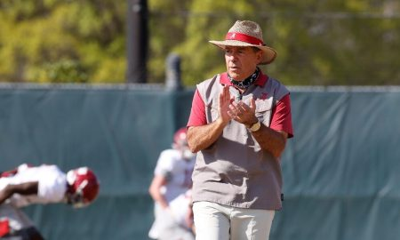 Nick Saban walks along the practice field