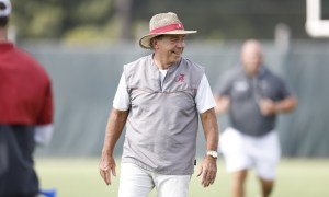Nick Saban smiling on the field as Alabama is in practice