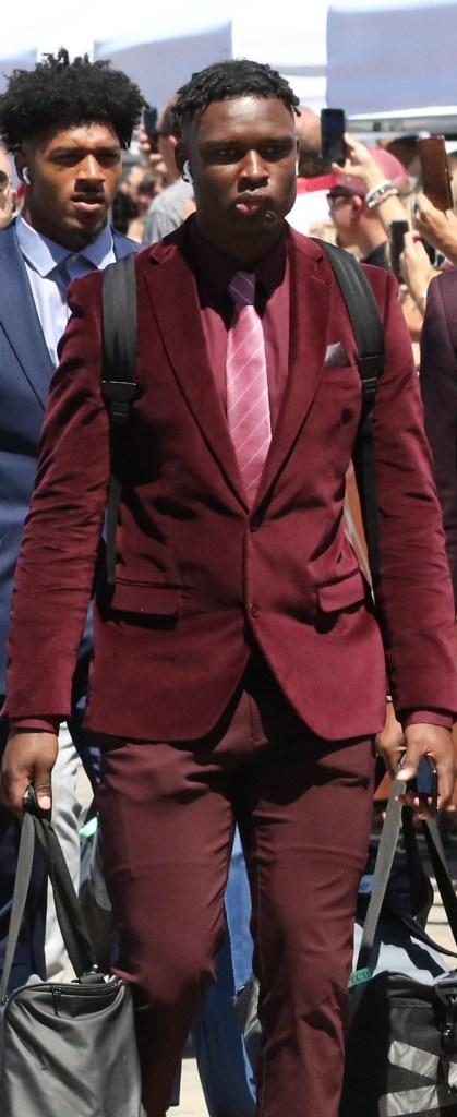 Jordan Battle walking in a burgundy suit