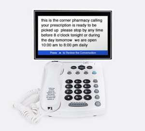 """White landline style phone with large screen attached to phone displaying captioned text of phone conversation """"this is the corner pharmacy calling..."""""""