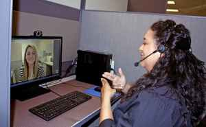 """Female person of color with long dark wavy hair wearing telephone headset looking at a computer signing """"name"""". On computer screen is white female with blonde hair smiling."""