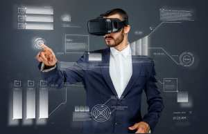 white male dressed in metallic blue suit with white shirt, wearing virtual reality headpiece pointing at superimposed computer generated images, representing what he is seeing inside the headpiece.