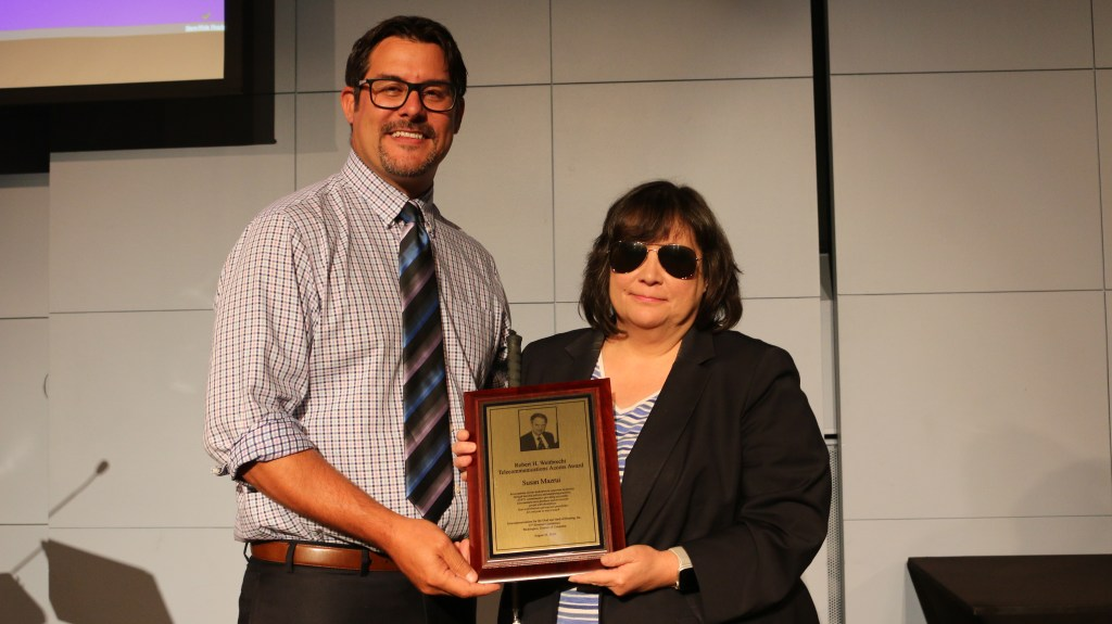 While male with dark hair and glasses wearing plaid button down shirt with tie holding a plaque with a white female with dark hair wearing sunglasses and dark jacket.