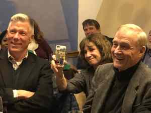 three people are immediately seen with few others in the background. To the left is a while male, white hair crossed arms smiling. In the middle is a white female smiling while holding a smartphone. To her right is a white male with a wide smile, almost laughing.
