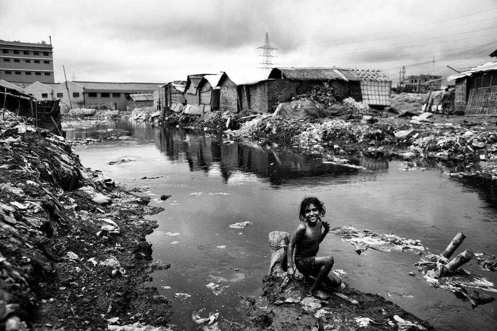 Kids play where trash and toxic chemicals fill canals which flow out into the Buriganga River. Hazaribagh was just listed in a report by Green Cross Switzerland and Blacksmith Institute as the 5th most polluted place on earth. It houses 95% of Bangladesh's leather tanneries. [Image: Unframed]