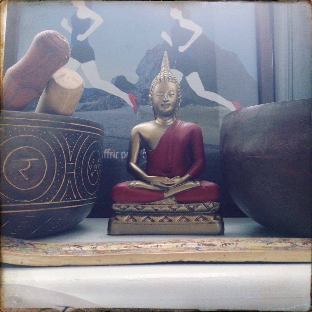 Buddha sitting, so very peacefully, between three singing bowls.