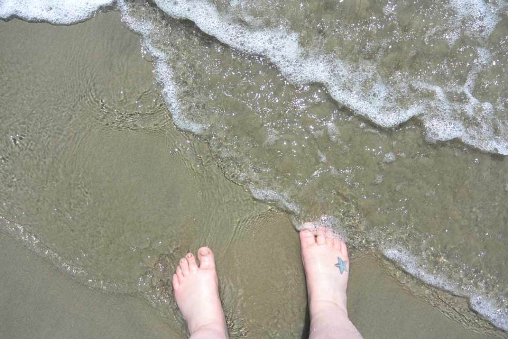 Top view of two feet on the sand with waves washing over them. Right foot has a blue star tattoo.