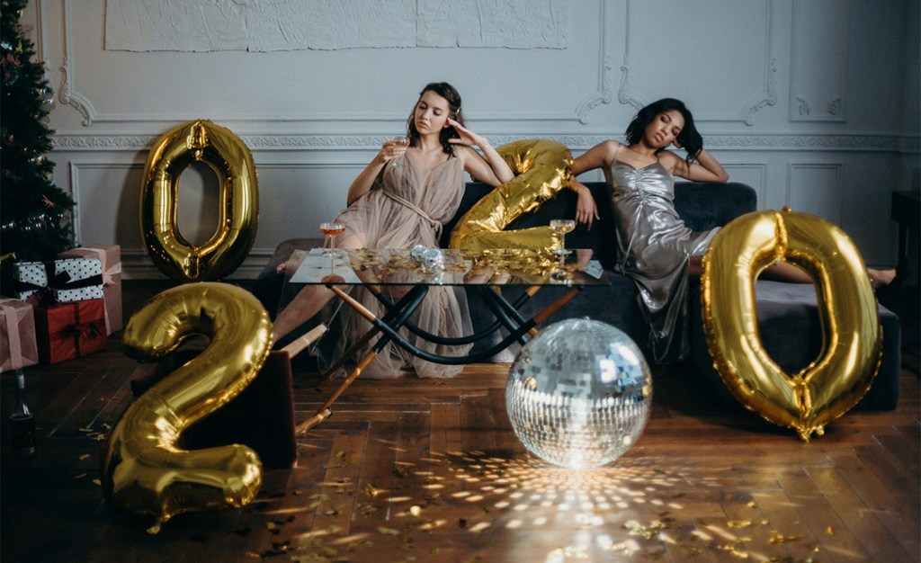Women tired from making choices in the new year. Sitting with balloons on a sofa, after party
