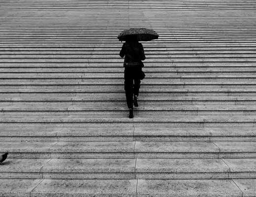 Woman with umbrella walking up many steps toward her goal