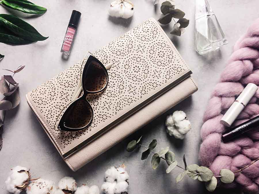 Sunglasses, a clutch, makeup and cotton scattered around