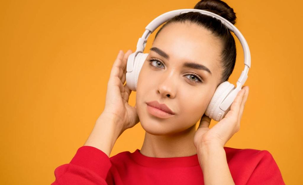 woman listening to headphones on bright background