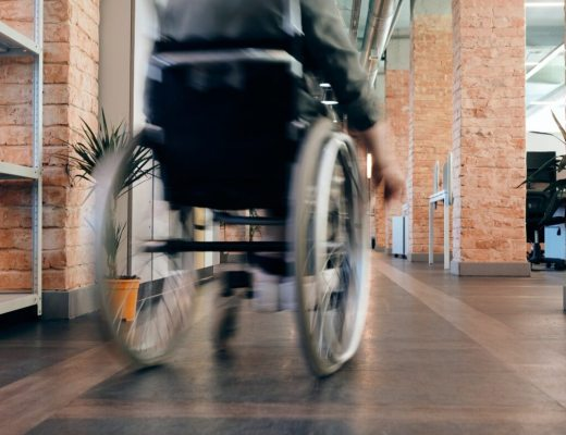 blurry wheelchair zooming down a corridor, disability pride