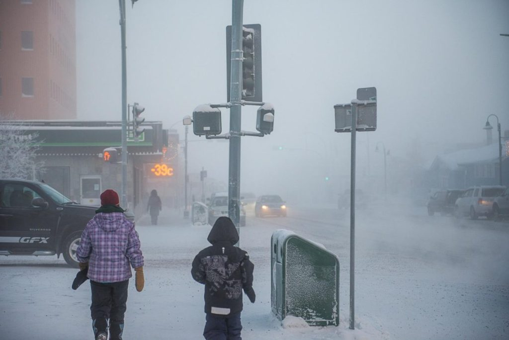 A street corner in a blizzard, a woman and child (bundled up from head to toe) wait to cross at the light. A sign with lights that reads -39°C. Burrrr!