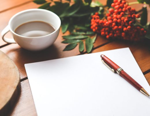 A cup of tea on a desk beside a blank piece of paper ready for the quick poetry challenge!