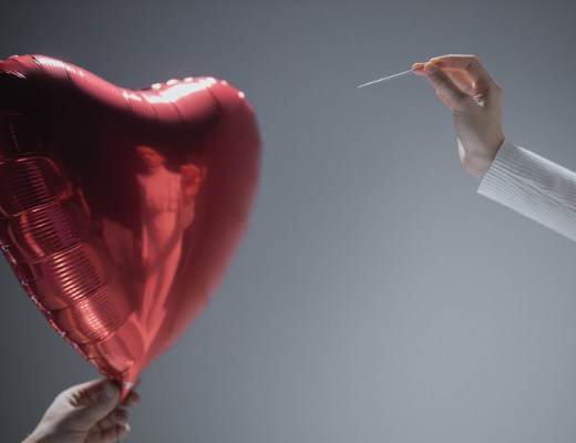Inflation blows! Image of red heart shaped balloon about to be burst by a pin held in a woman's hand