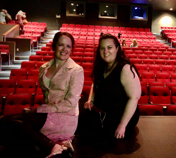 Amber and Myranda pose onstage with the seating in the background