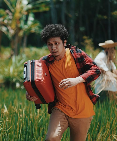 Man running through a field with a piece of luggage