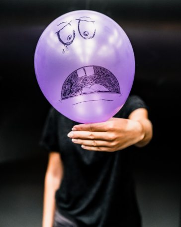 Person holding purple balloon with a sad face drawn on it because inflation blows