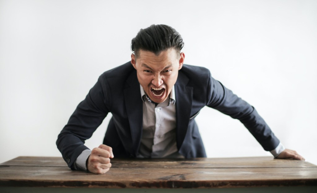 Angry Asian man pounding his fist on the table, over the top anger in his negative review