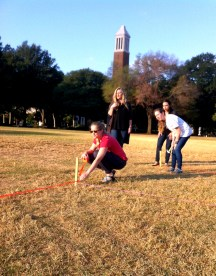 students using stakes and twine to create a cathedral shape on the Quad
