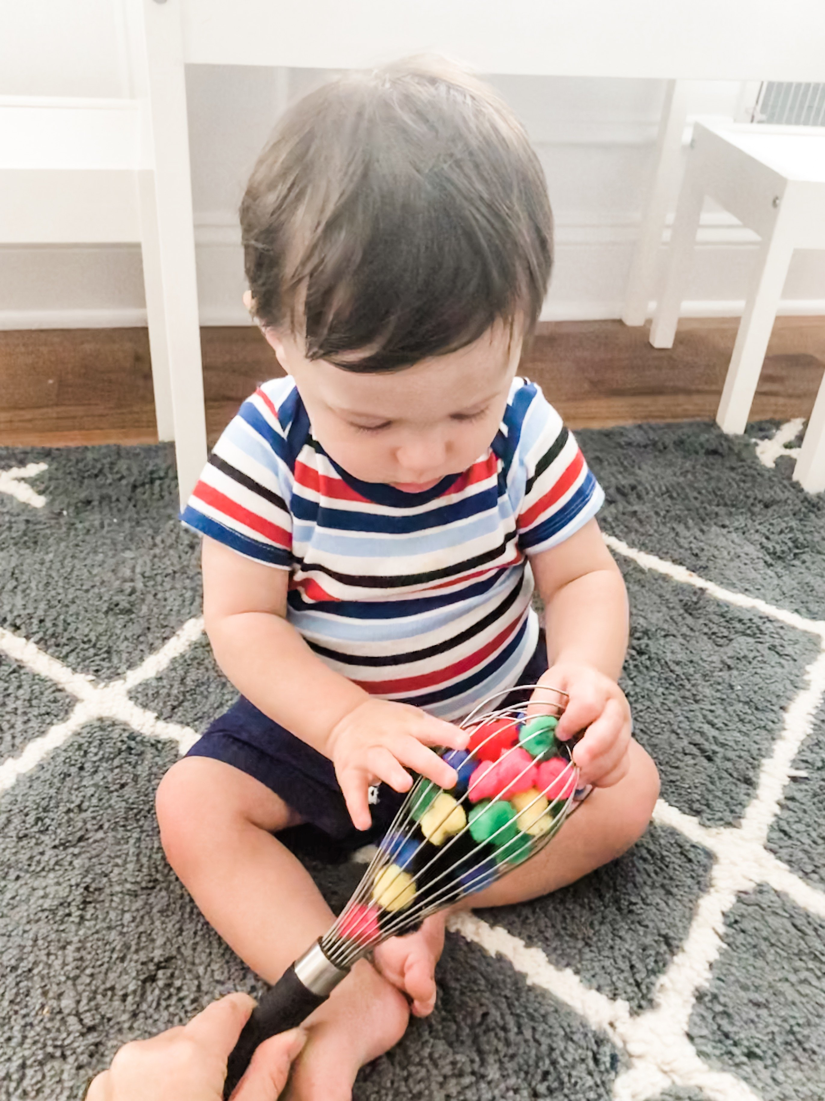 This pompom whisk baby activity works on fine motor skills and learning. Using colored poms is a great fine motor activity for infants 9 months or older.