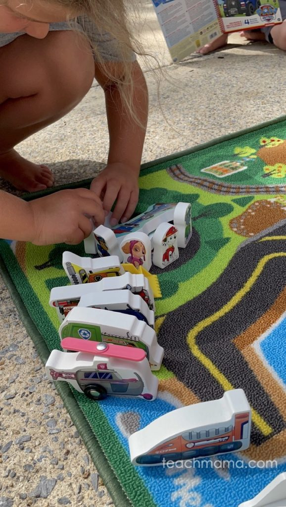 little girl playing on carpet with paw patrol figures