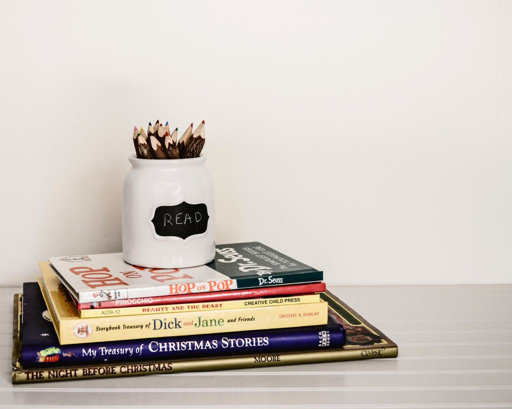 A stack of 6 children's books, including Dr. Seuss, Dick and Jane, and Christmas stories. A white jar full of colored, wooden pencils rests on top of the stack of books