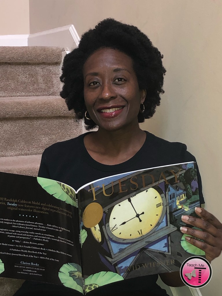A picture of Tania N. Davis (me) smiling and holding the book, Tuesday by David Wiesner, in my hands while I am sitting on the stairs.