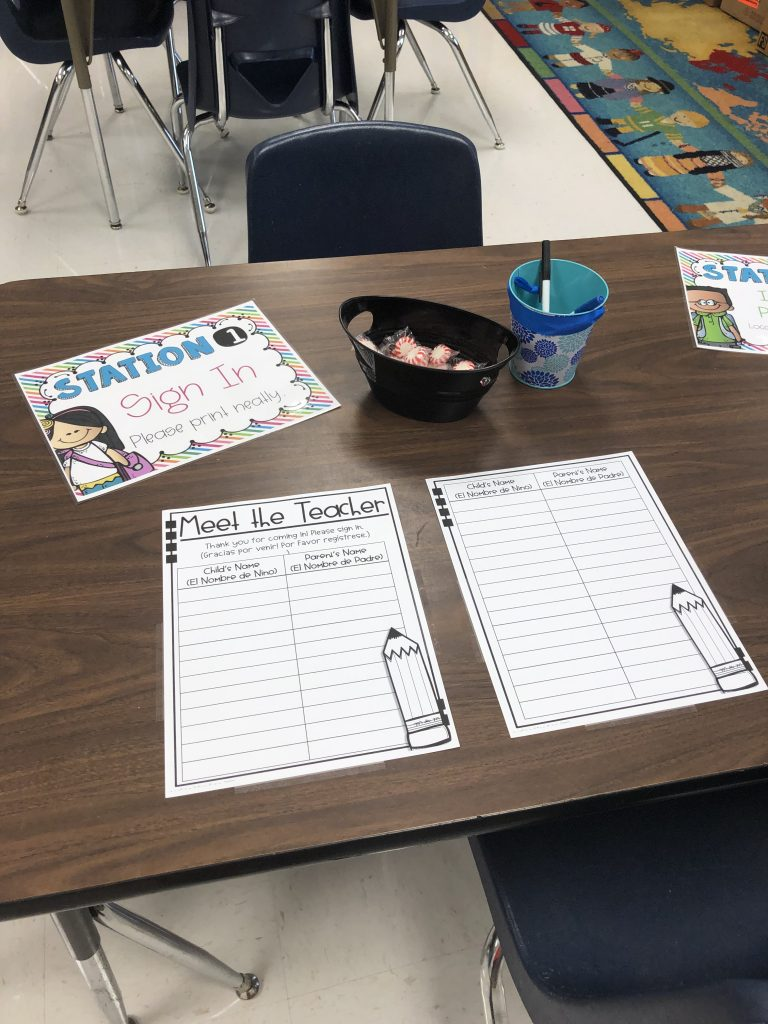A photograph of my sign-in table during Meet the Teacher. There is a brown, wooden table with a sign for signing in, a Meet the Teacher Sign-In sheet that it is written in English and Spanish, a black bowl of peppermint candies, and a blue pencil cup full of pens.