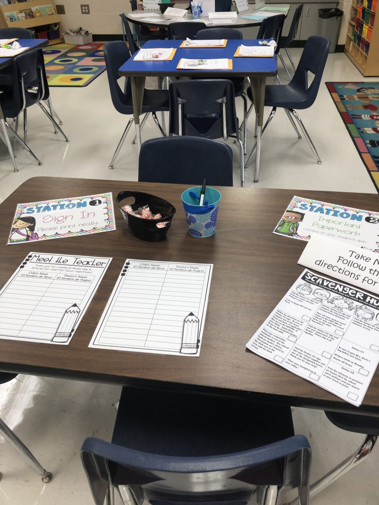 An image of a wooden, classroom table that has been set up with forms, pens, and mints to greet parents during Meet the Teacher.