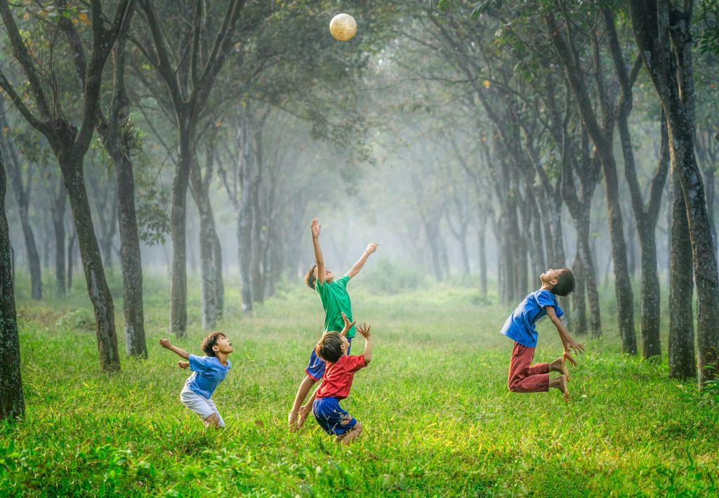 A photo of 4 young boys playing with a ball in bright grass that has trees lining both sides.  They are playing while the sprinklers are on.  The boys are jumping up to see who can hit the ball first.
