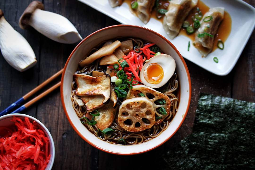 An aerial shot of the vegetarian shiitake mushroom ramen, with pickles and gyozas on the side.