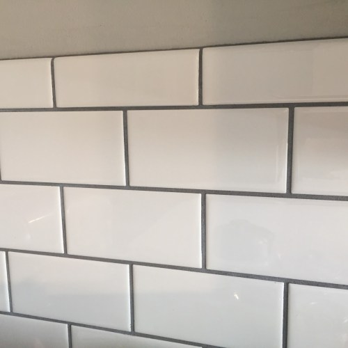 white subway tile backsplash with dark gray grout