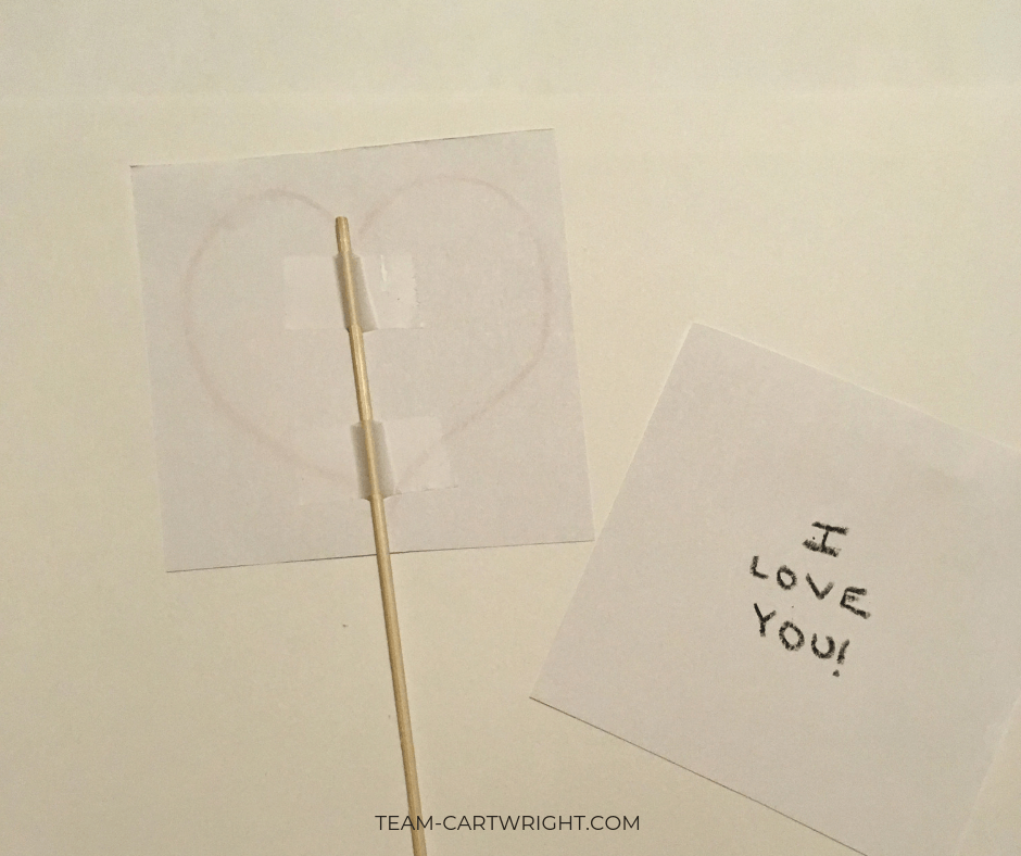 Thaumatropes for kids Step 2: Tape the skewer into place! #Thaumatrope #ValentineCard #ValentineSTEM #HomemadeValentine Team-Cartwright.com