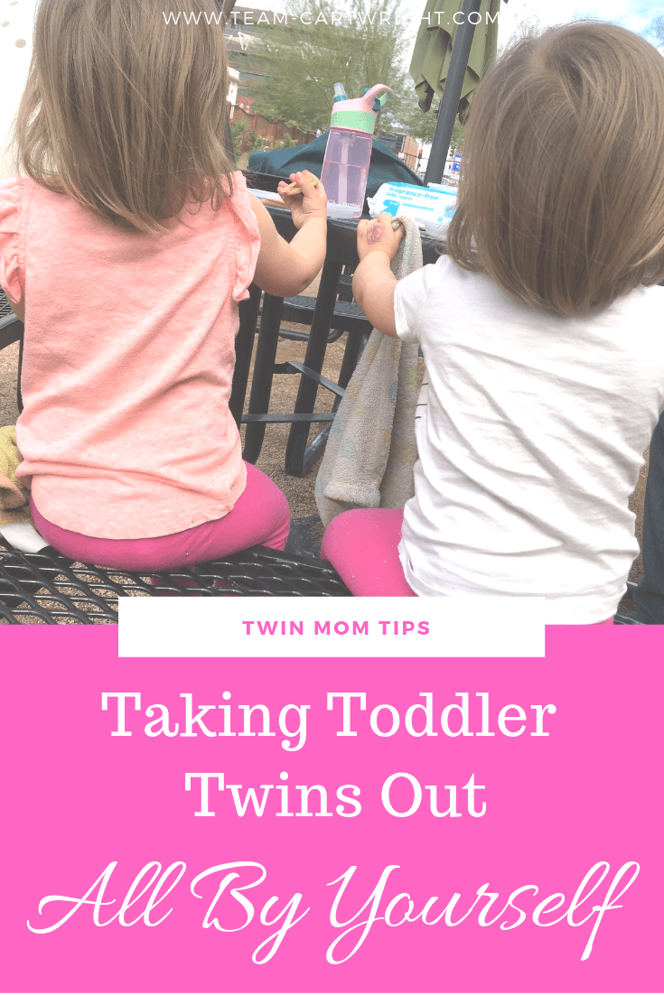 Twin girls sitting at table with text overlay Taking Toddler Twins Out All By Yourself