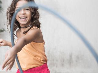 Preschool girl playing with hula hoop