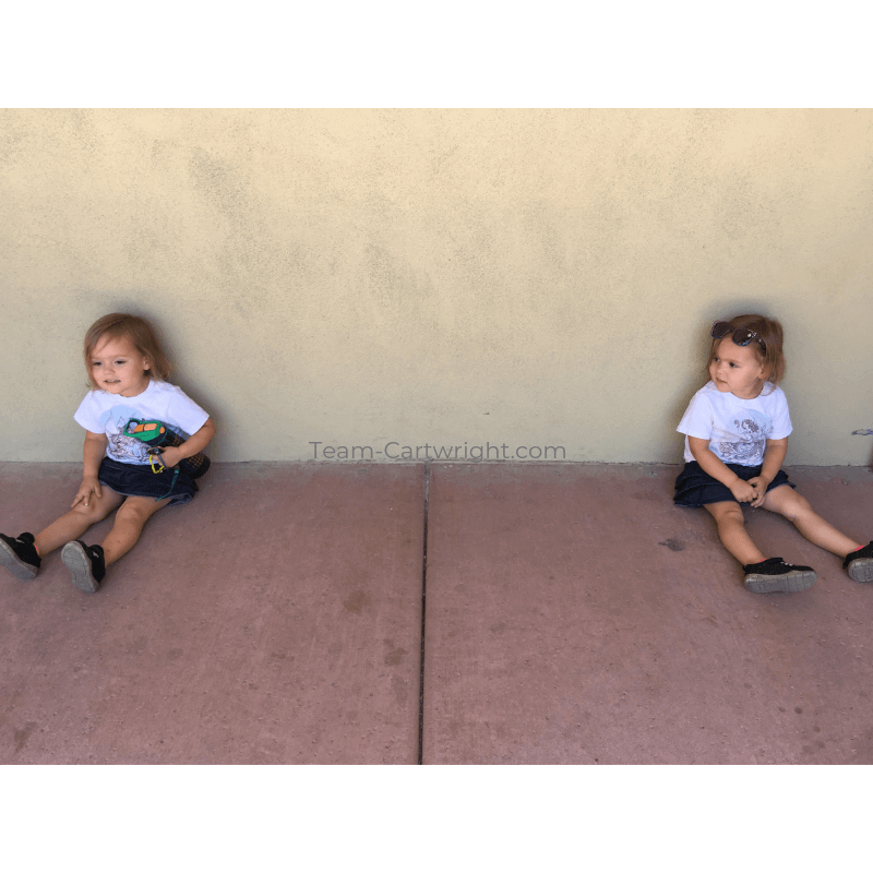 picture of twins sitting a few feet apart against a wall
