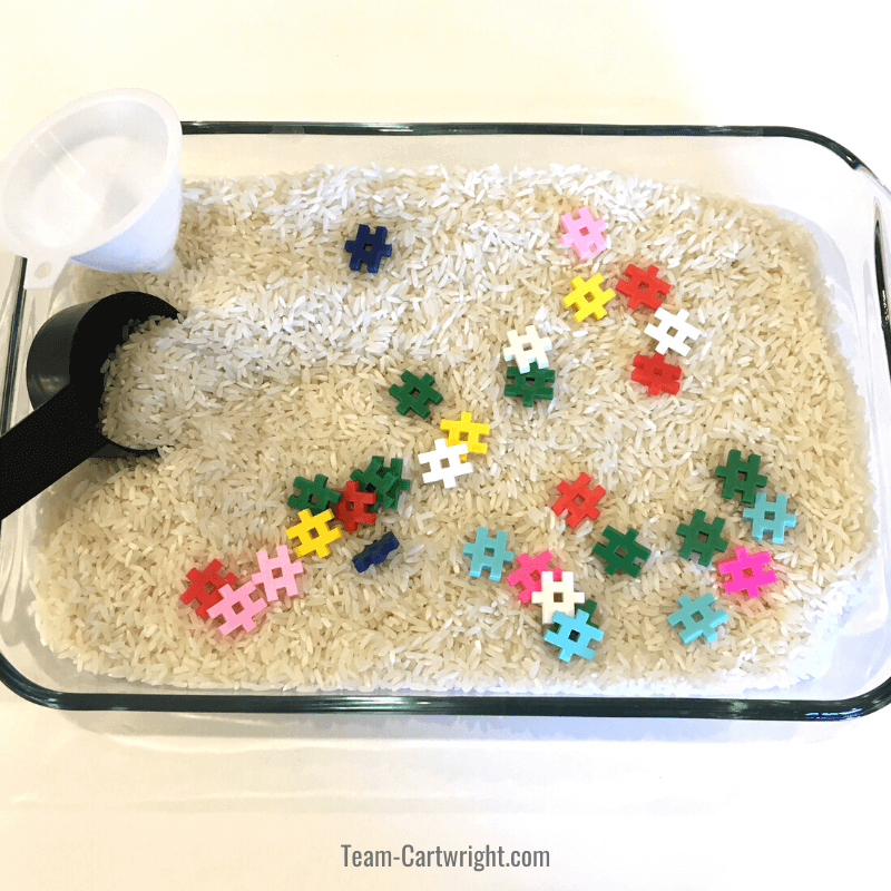 Rice sensory bin with funnel, measuring cup, and colorful waffle blocks