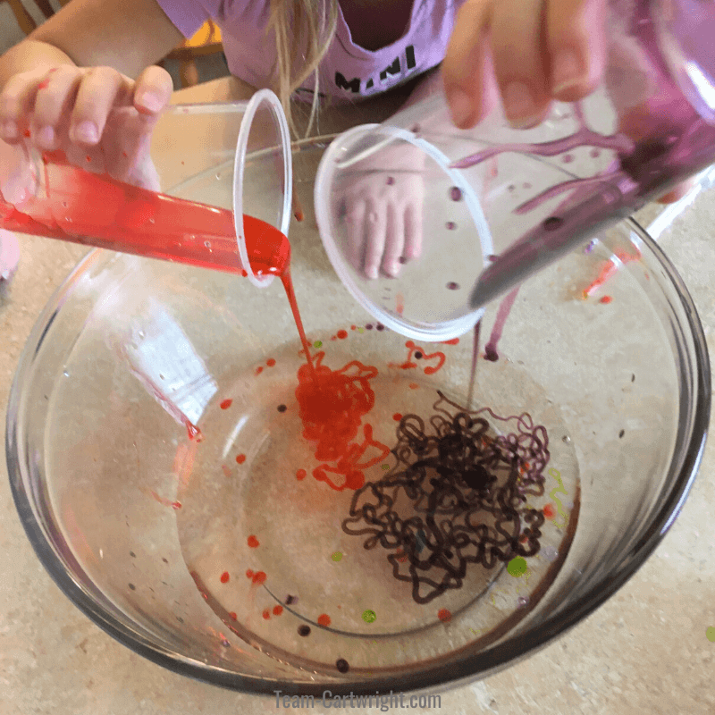 picture of children mixing solutions to make slime worms