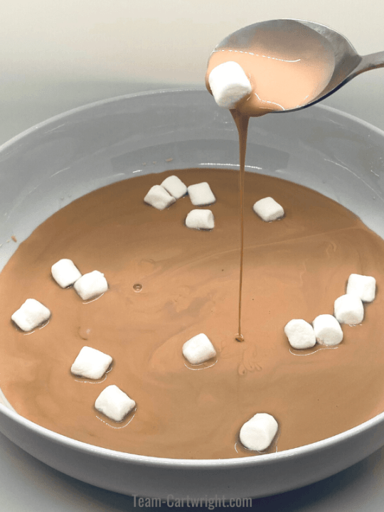 picture of hot chocolate oobleck falling out of a spoon with marshmallows