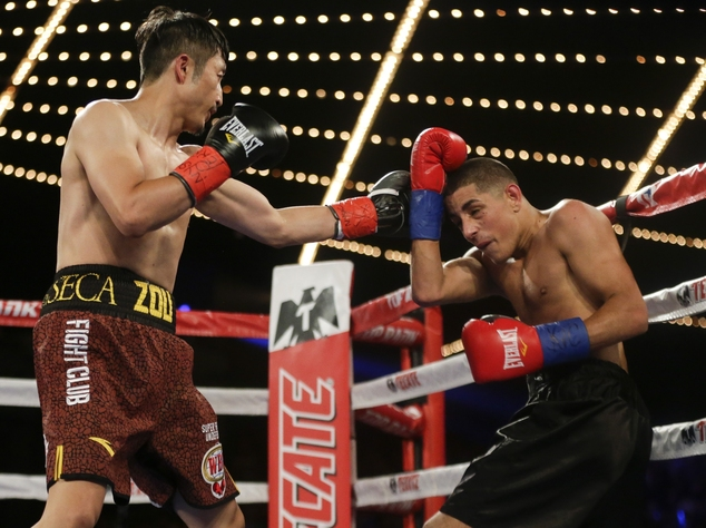Zou Shiming, left, of China, punches Jozef Ajtai, of Hungary, during the second round of a WBO flyweight title boxing match Saturday, June 11, 2016, in New York. Zou won the fight. (AP Photo/Frank Franklin II)