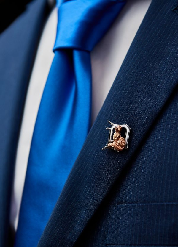 a small fox lapel pin on a suit