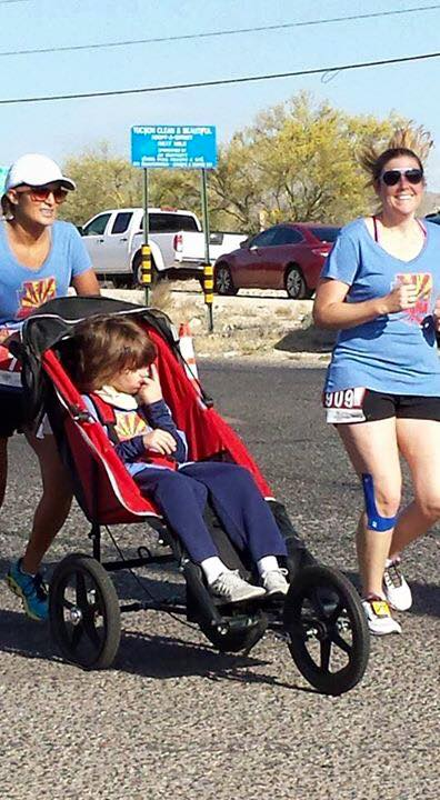 A photo of a boy (Brett) in his race wheelchair pushed by a smiling Team Hoyt Arizona athlete, next to another running smiling teammate. All three are wearing blue team shirts with the red and gold Team Hoyt Arizona flag on the front.
