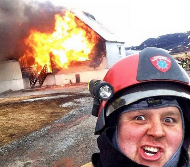 Funny fireman photobomb in front of burning house