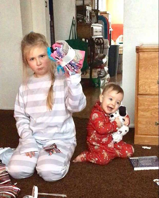 Easy to see who Santa loves best ~ Funny  Family Christmas Photos ~ sister dissed, socks for present